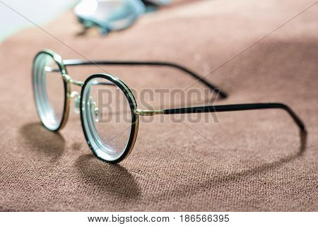 Blurred close-up a glasses on brown garment. selective focus and with a very shallow depth field.