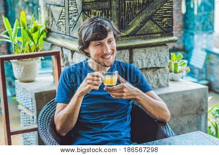 Young Man Sitting In A Cafe Drinking A Delicious Morning Ginger Tea In A Cafe