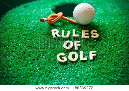 Rules of golf word with golf ball on green grass