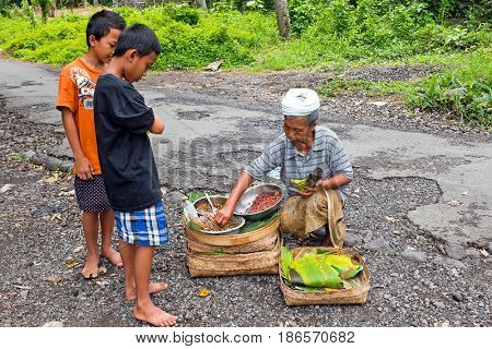 BALI, INDONESIA - DECEMBER 25, 2016: Balinese elder woman brings food to young boys in the countryside from Bali on 25th of december 2016