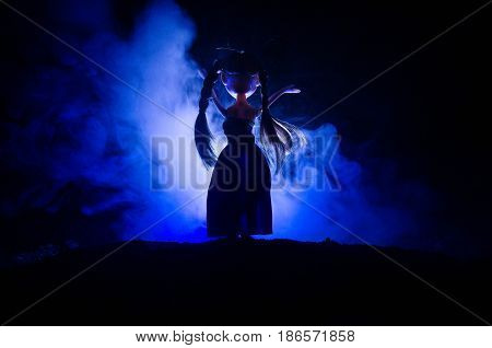 Silhouette of mysterious Woman Horror scene of scary ghost doll woman on dark blue background with smoke