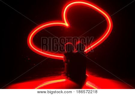 Two young lovers paint a heart on fire. Silhouette of couple and Love words on a dark background. Love concept