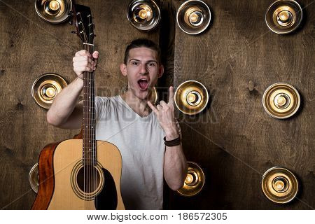 Guitarist, Music. A Young Guy Is Standing With An Acoustic Guitar In His Hand, In The Background Wit