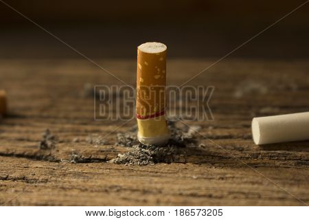 cigarette butt with ash on wooden tableconcept for wolrd no tobacca day.