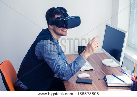 Young businessman putting on vr glasses and smiling. Virtual reality in office