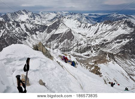 MUNKU-SARDYK BURYATIA RUSSIA-April 292017: Climbing peak of Munku-Sardyk in background of mountain massif. Mountaineers move around with their hands on rope