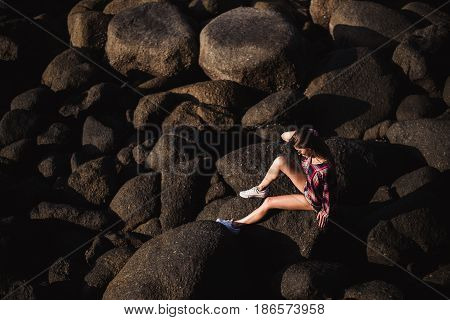 Sexy woman in jeans overall and pink t-shirt sit on big stone at rock beach sea ocean shore. Modern hipster girl have fun. Good sunny summer day.