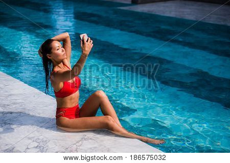 Beautiful woman in bikini taking a selfie by pool side on a sunny day at luxury hotel.