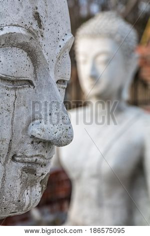 Close-up profile of a cement buddha statue with another buddha statue in soft focus behind it
