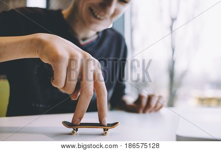 Funny and handsome guy sitting in a nice cafe near the window and playing on the table with a small toy. Smilng man is happy. Close up