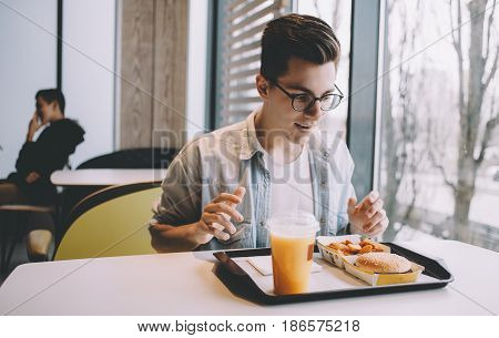 Handsome young man having lunch in a cool cafe alone. Dlighted guy in eyeglasses has big and hungry eyes. He is ready to attack his meal.
