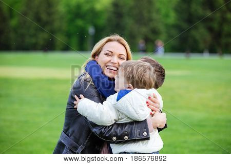 Happy young woman hugging two sons and laughing in park