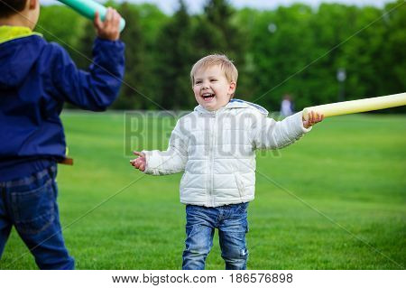 Two brothers playing with toy swords and laughing in park