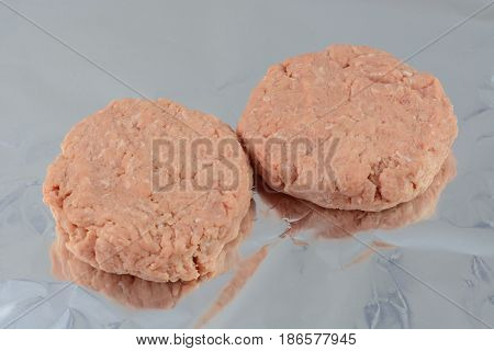 Two raw ground turkey meat burgers on aluminum foil ready for grilling