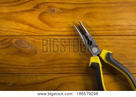 Close up of a multitool pliers on wooden background
