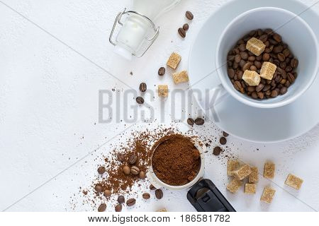 Ingredients for coffee: ground coffee in the horn of the coffee machine, sugar and a cup. Top view with copy space
