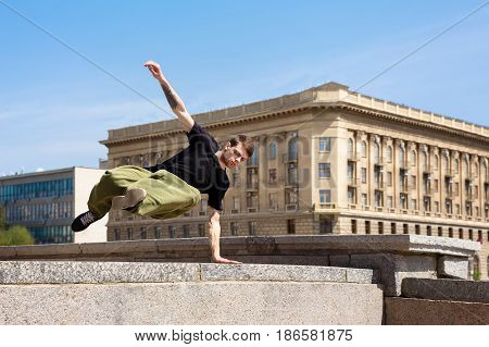 Young man jumping over the wall. Parkour in the urban space. Sport in the city. Sport activity.