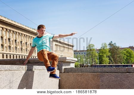 The young man jumps over the wall. Parkour in the urban space. Sport in the city. Sport activity.