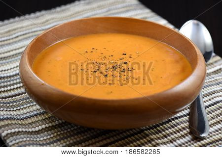 Creamy tomato soup with black pepper in a wooden bowl