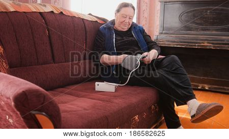 Portrait of an elderly woman who is sitting on the couch and wants to measure himself blood pressure electronic device