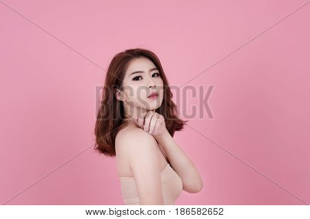 Short Hair Asian Young Beautiful Woman Smile And Point On Her Head, Isolated Over Pink Pastel Backgr