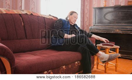 Portrait of an elderly woman in home clothes, sitting on a brown sofa, runs a hand over the handset