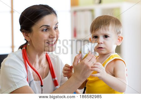 Doctor helps to kid with runny nose