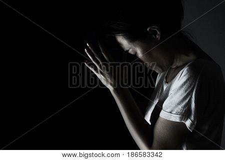 Depress Woman Praying In The Dark ( Praying In Secret Room Concept )