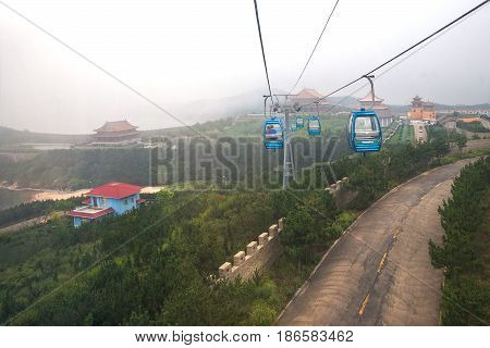 Weihai, China - July 31, 2014: Cabin cableway in air above Chengshantou Scenic Area, near Weihai, top view