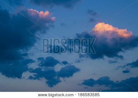 Beautiful bright colorful pink red yellow orange clouds on dark light blue sky at sunset sunrise evening or morning time background with copy space