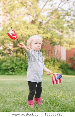 Happy adorable little blond Caucasian girl holding waving American and Canadian flag in park outside celebrating 4th july Independence Day Canadian Day friendship support