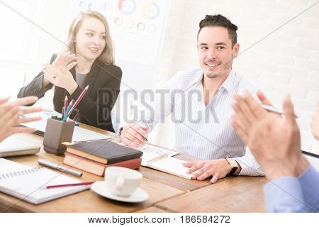 Business people clapping hands to congratulate their colleague at the meeting