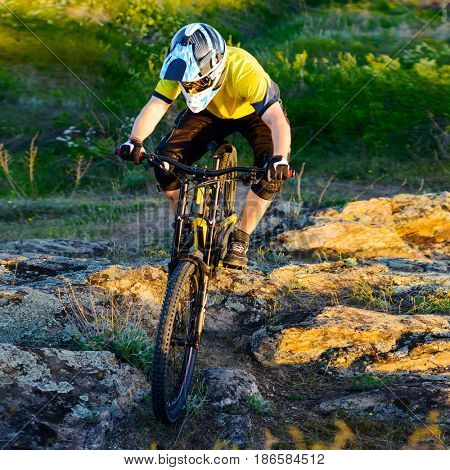 Cyclist in Yellow T-shirt and Helmet Riding the Mountain Bike Down Rocky Hill. Extreme Sport Concept.