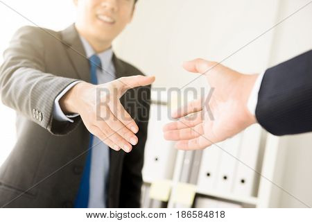 Businessmen making handshake in the office - greeting dealing merger and acquisition concepts