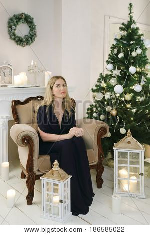 Woman in black dress sits in armchair in room with christmas tree and lanterns on floor