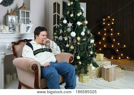 Boy teenager in jeans sits in armchair in room with christmas tree and illuminated tree