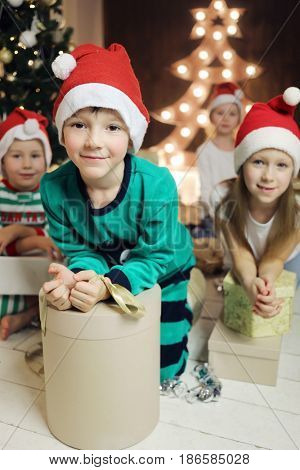 Two little boys, two girls with gifts in boxes are in room with christmas tree, focus on boy in green