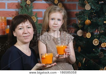 Woman and her little daughter hold candles in glasses near christmas tree in brick room, focus on mother
