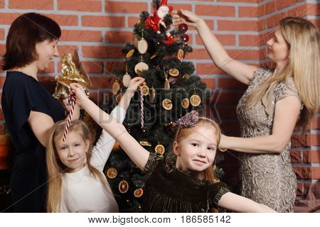 Girrl pose, two women with girl decorate christmas tree out of focus in room