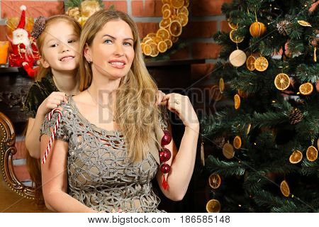 Happy blonde woman with little daughter pose near christmas tree in room, focus on mother