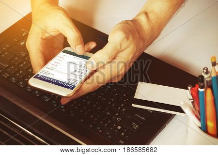 Man's Hands Using Smartphone For Online Banking On The Desk In The Office Or Home.