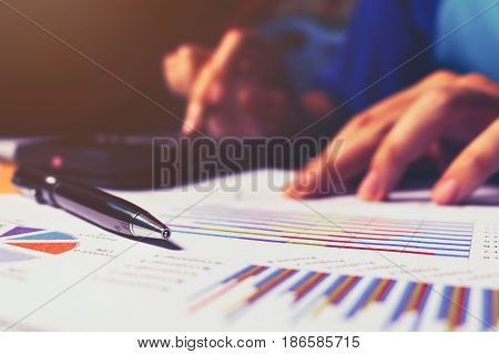 Close Up Of Pen On Summary Report And Woman Doing Calculate Finance.