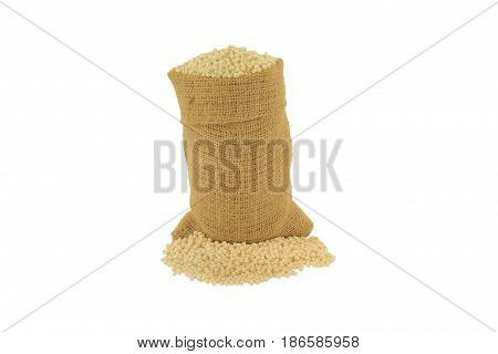 Raw (uncooked) Israeli Couscous in burlap bag and spilled out on pile over white background - isolated