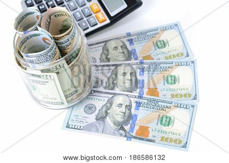 Money US dollar bills with calculator on white table - financial and accounting concepts