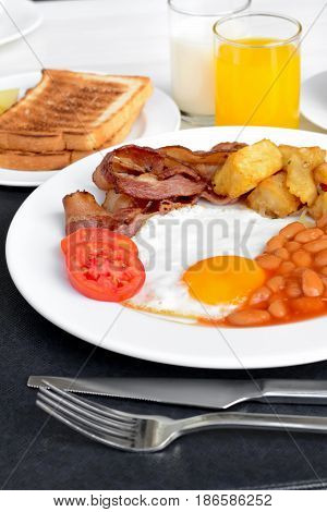 English breakfast including fried egg baked beans potato bacon some bread juice and milk