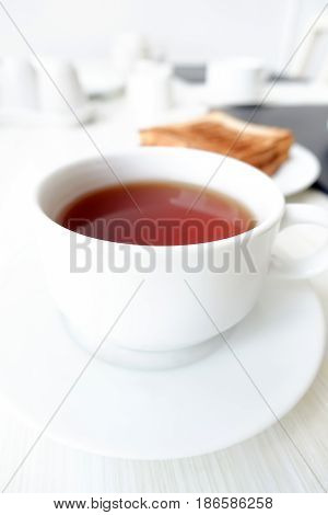 Hot tea in white cup with blur toast on the table as background breakfast concept - soft focus
