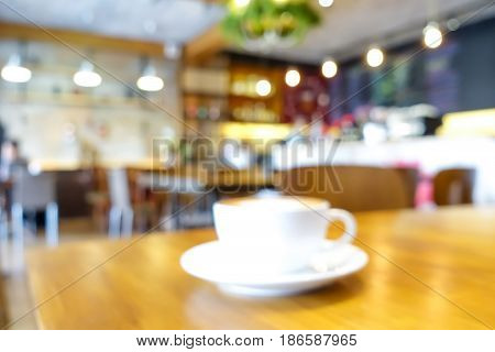 Blur coffee shop interior with a cup of coffee on the table -can be used as background