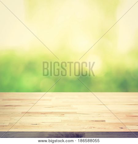 Wood table top on green bokeh abstract background vintage tone - can be used for montage or display your products