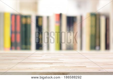 Wood table top on blur bookshelf background - can be used for display or montage your products