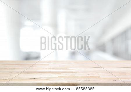 Wood table top on blurred white gray background of building hallway - can be used for display or montage your products